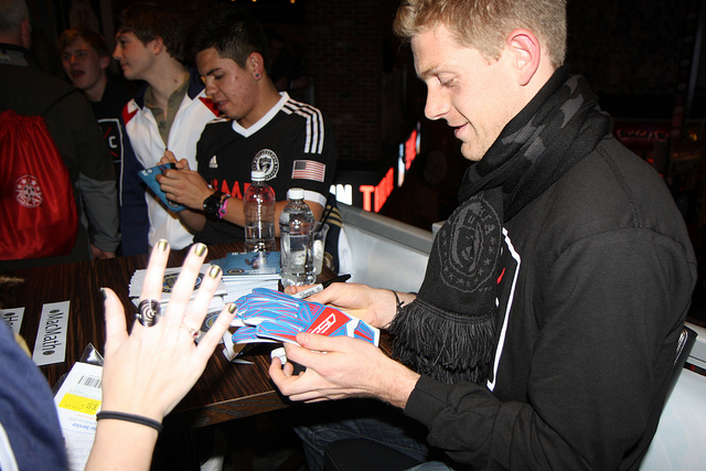 Zac MacMath signs a couple of gloves