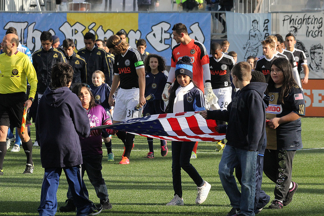 Young fans help out with the flag in the beginning of the match
