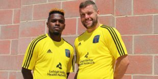 Photo courtesy of Bethlehem Steel FC. Chris Nanco and James Chambers pose while wearing the special gold warmups for match benefiting PCFLV.