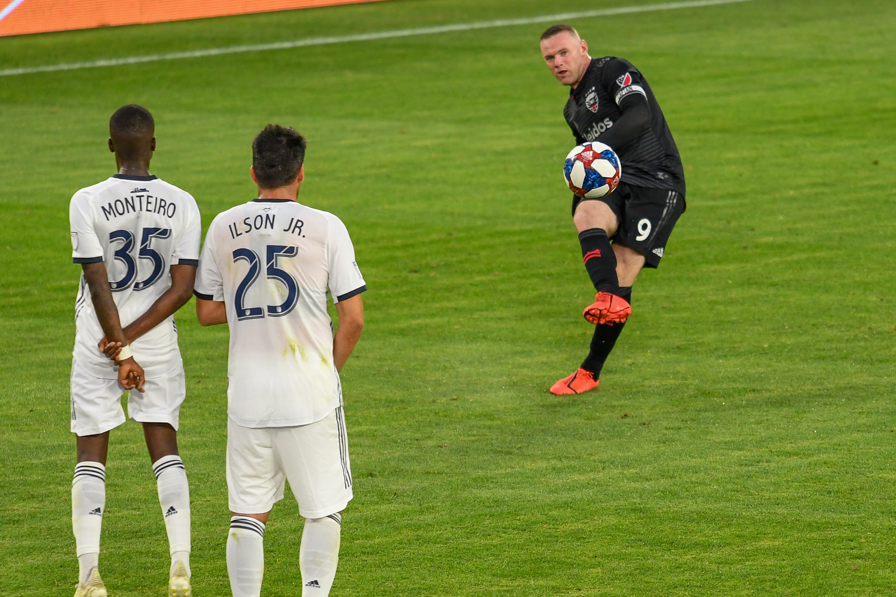 Wayne Rooney (9) takes a penalty kick with Monteiro (35) and Ilsinho(25) making the wall.