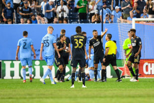 Monteiro watches as his teammates Medunjanin, Bedoya, and Trusty argue a yellow card caution.