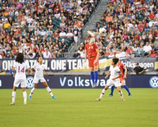 Julie Ertz gets a header from a corner kick.