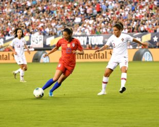 Christen Press handles the ball with slight pressure from Monica Mendes.