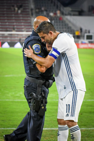Bedoya and an officer at the field share am embrace and a few words after the game.