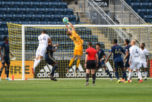 Morton makes a great save, jumping to get his hands on the ball. His teammates look on ready to assist him if needed.