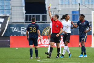 A yellow card was issued to Zach Zandi which prompted the scuffle between Sergio Santos and Zach Herivaux behind the ref's back. Both were issued red cards and left the game.