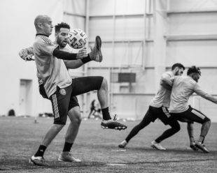 Aurelien Collin and Andrew Wooten battle for the ball during defensive drills. Matt Real and Olivier Mbaizo are pictured fighting it out in the same drill.