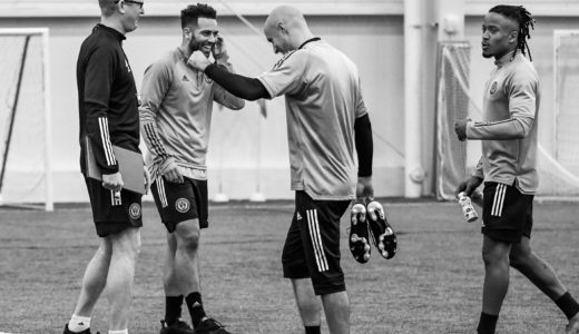 Coach Curtain jokes with Andrew Wooten and Aurelien Collin after practice while Sergio Santos enters the conversation.