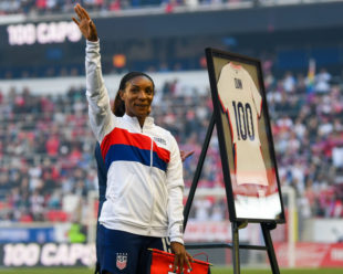 Crystal Dunn waves to the crowd, saluting them for supporting her, while she is presented with her Jersey cementing her accomplishment of 100 Caps with the USWNT.