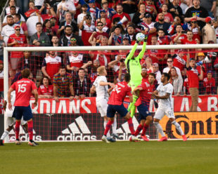 Andre Blake uses is height to jump and make a great save against a backdrop of fans hoping to celebrate.