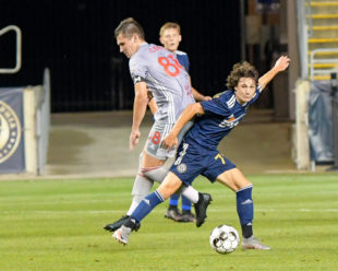 Paxten Aaronson takes on Red Bulls 2, Deri Corfe during his debut game.