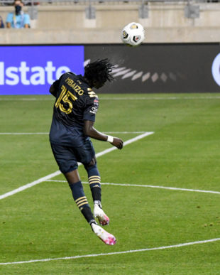 Olivier Mbaizo makes a defensive play heading the ball outside the box.