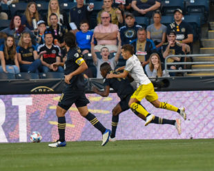 Pedro Santos jumps on the back of Cory Burke to stop a possible shot on goal. Santos received a yellow card for his actions on the play.