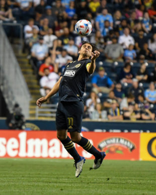 Captain, Alejandro Bedoya jumps to receive the ball with his chest during the game.