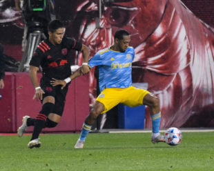 Jose Martines focuses on the ball while keeping Wike Carmona an arms length away.