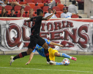 Kia Wagner slides into the ball, stopping Fábio Roberto Gomes Netto from taking it up the field.