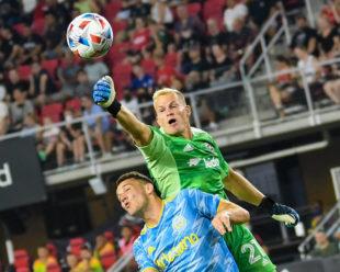 Jon Kempin punches the ball over the head of Daniel Gazdag.